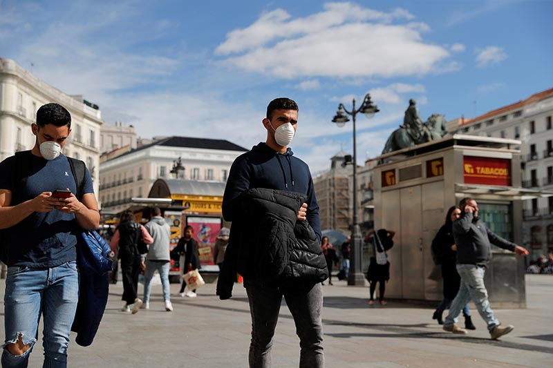 Men wear protective masks as they walk through Puerta del Sol square in Madrid, Spain, on March 4, 2020. Photo: Reuters