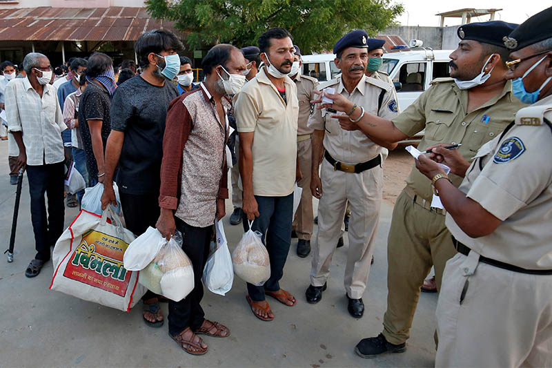 Police officers speak with prisoners after they were released on parole outside the Sabarmati Central Jail during a 21-day nationwide lockdown to slow the spreading of coronavirus disease (COVID-19), in Ahmedabad, India, March 30, 2020. Photo: Reuters