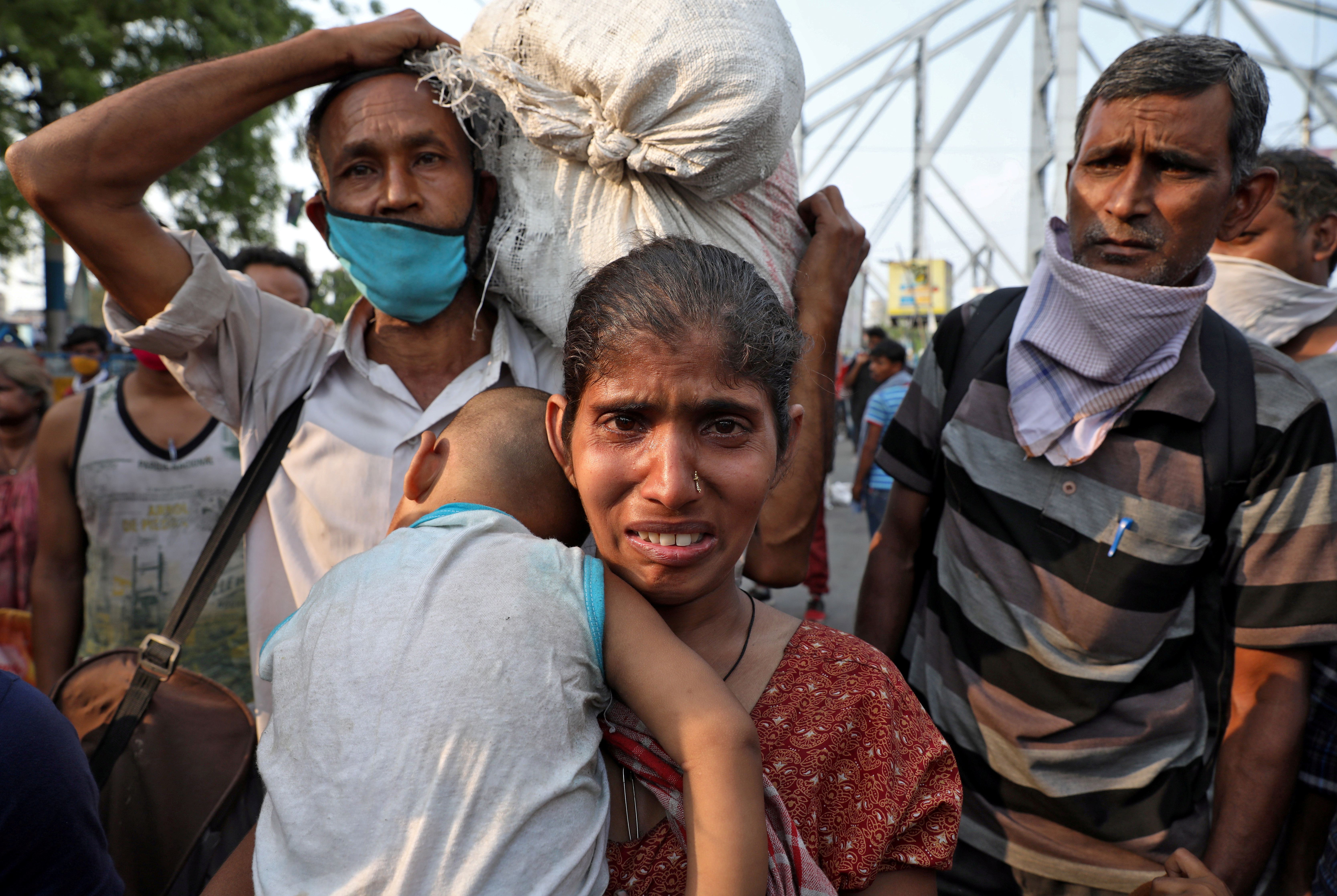 A migrant worker holding her baby cries after she missed out on receiving free food outside Howrah railway station after India ordered a 21-day nationwide lockdown to limit the spreading of coronavirus disease (COVID-19), in Kolkata, India, March 25, 2020. Photo: Reuters