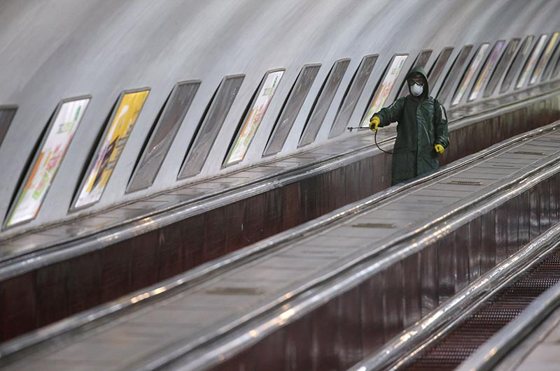 An employee wearing protective gear rides an escalator while spraying disinfectant to sanitize a metro station over coronavirus fears in Tbilisi, Georgia March 3, 2020. Photo: Reuters