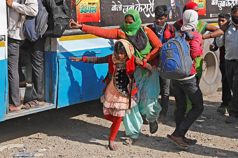 A migrant worker holds her daughter's hand as she tries to board a crowded bus to return to her village, during a 21-day nationwide lockdown to limit the spreading of coronavirus disease (COVID-19), in Ghaziabad, on the outskirts of New Delhi, India, March 29, 2020. Photo: Reuters