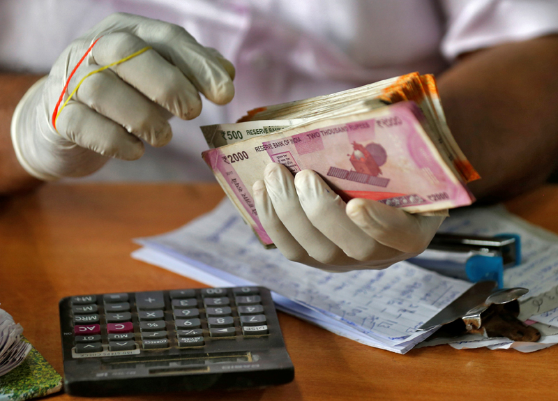 A trader wearing protective hand gloves counts Indian currency notes at a market during a 21-day nationwide lockdown to limit the spreading of coronavirus disease (COVID-19), in Kochi, India, March 27, 2020. Photo: Reuters