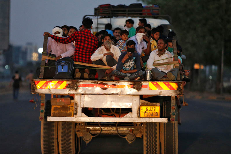 Migrant workers and their families travel in a trailer truck as they return to their villages during a 21-day nationwide lockdown to limit the spreading of Coronavirus disease (COVID-19), on the outskirts of Ahmedabad, India, March 29, 2020. Photo: Reuters
