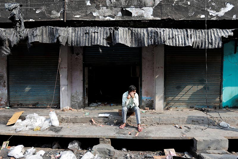 A man sits in front of burnt out properties owned by Muslims in a riot affected area following clashes between people demonstrating for and against a new citizenship law in New Delhi, India, March 2, 2020. Photo: Reuters