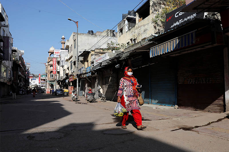 A woman walks along a near-empty street during a lockdown amid a coronavirus disease (COVID-19) outbreak in New Delhi, India, March 25, 2020. Photo: Reuters