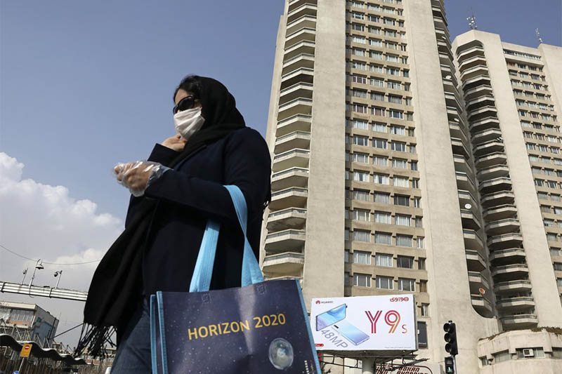 A pedestrian wearing a face mask crosses a street in northern Tehran, Iran, Sunday, March 1, 2020. While the new coronavirus has extended its reach across the world, geographic clusters of infections were emerging, with Iran, Italy and South Korea seeing rising cases. Photo: AP