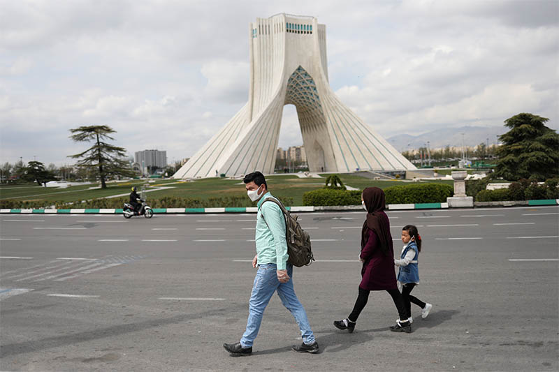 A family wear protective face masks and gloves, amid fear of coronavirus disease (COVID-19), as they walk by the iconic Freedom Square, in Tehran, Iran March 26, 2020. Photo: Reuters