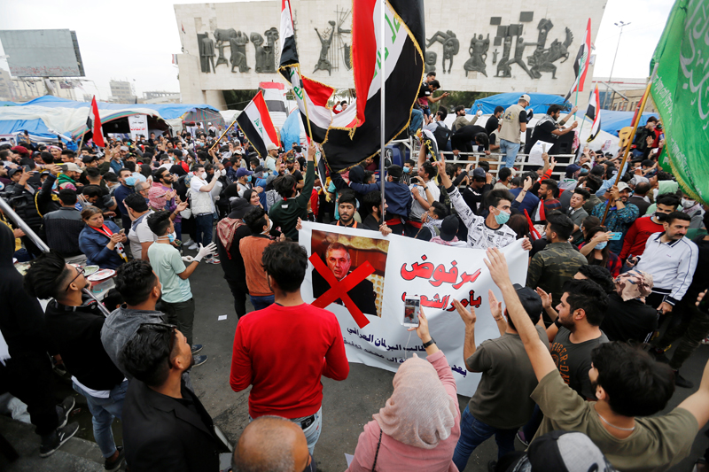 Iraqi demonstrators carry a poster depicting the Prime Minister of Iraq, Mohammed Tawfiq Allawi, to express their rejection of him, during ongoing anti-government protests in Baghdad, Iraq March 1, 2020. Photo: Reuters