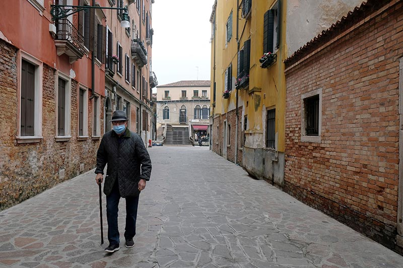FILE - An elderly man with a protective mask walks in Venice, on the fourth day of an unprecedented lockdown across all country, imposed to slow the outbreak of coronavirus, Italy March 13, 2020. Photo: Reuters