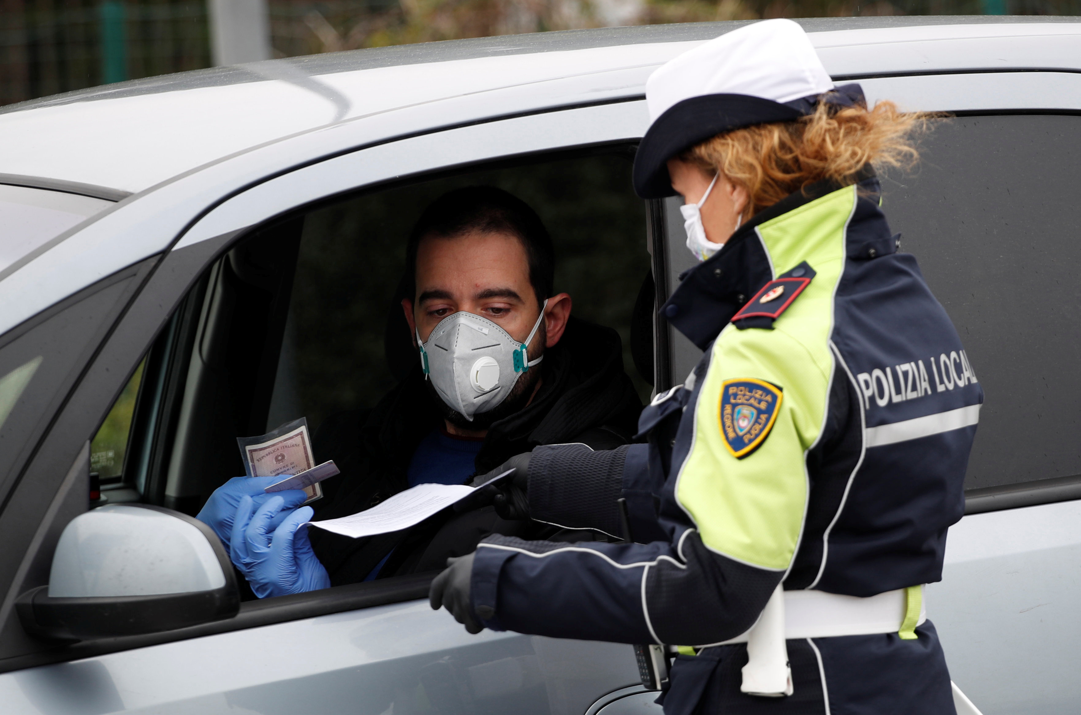 A local police officer checks on people at the Highway exit for Molfetta, southern Italy, March 25, 2020. Photo: Reuters