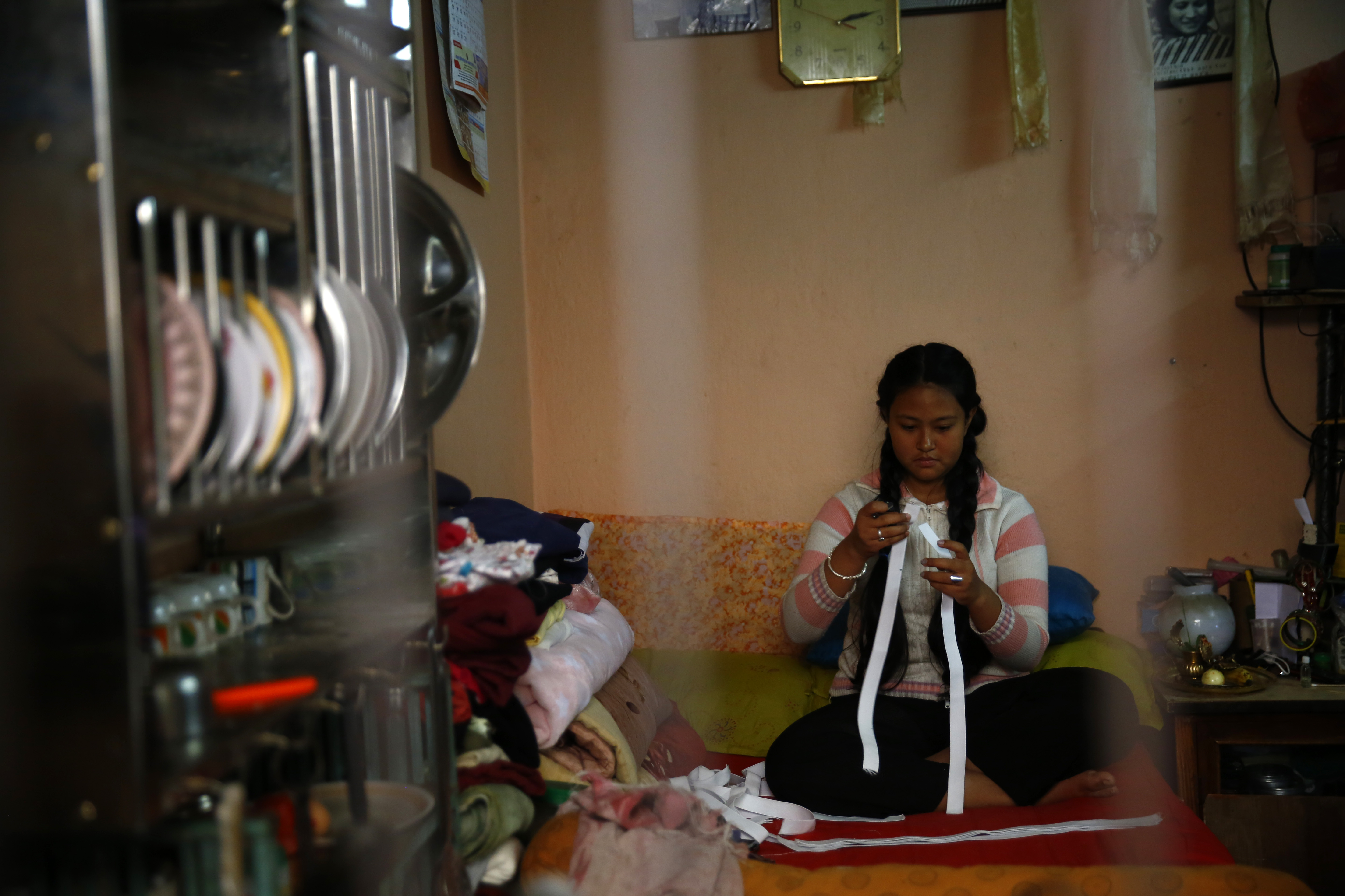 A girl makes protective face shields at her rented apartment, for security personnel, journalists and people on duty, on the fifth day of government-imposed-lockdown, amid concerns over spread of coronavirus infection, in Kathmandu, on Saturday, March 28, 2020. Photo: Skanda Gautam/THT