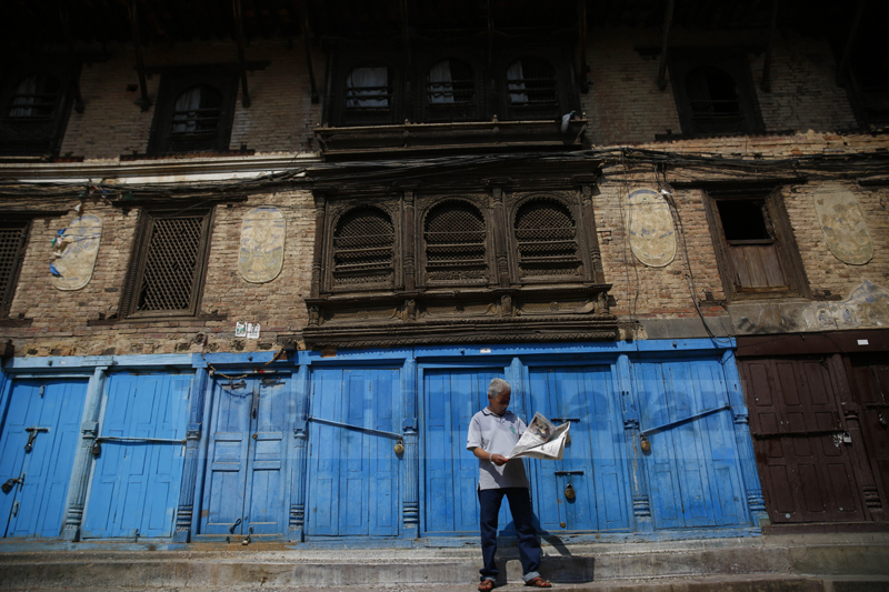 A man reads a paper in front of closed shops on the second day of the week-long nationwide lockdown, in Lalitpur, on Wednesday, March 25, 2020. Photo: Skanda Gautam/THT