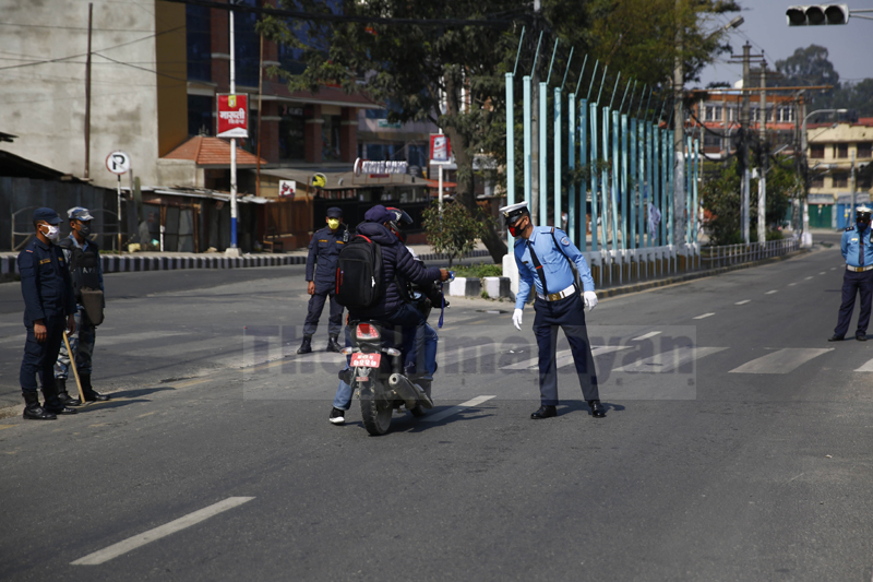 A policeman checks the documents for vehicles plying on the road on the second day of the week-long nationwide lockdown, in an effort to control the spread of COVID-19, in Kathmandu, on Wednesday, March 25, 2020. Photo: Skanda Gautam/THT