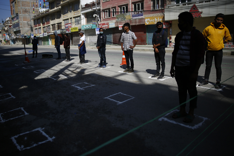 Detained violators stand on markings to maintain social distance, outside a Police Station in Kathmandu, on the sixth day of government imposed nationwide lockdown, Sunday, March 29, 2020. Photo: Skanda Gautam/THT