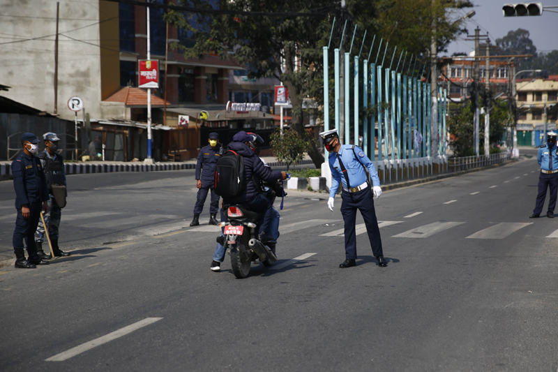 A policeman checking ID cards for vehicles plying on the streets on the second day of the week long nationwide lockdown in an effort to control the spread of COVID-19 in Kathmandu, on Wednesday, March 25, 2020. Photo: Skanda Gautam/THT
