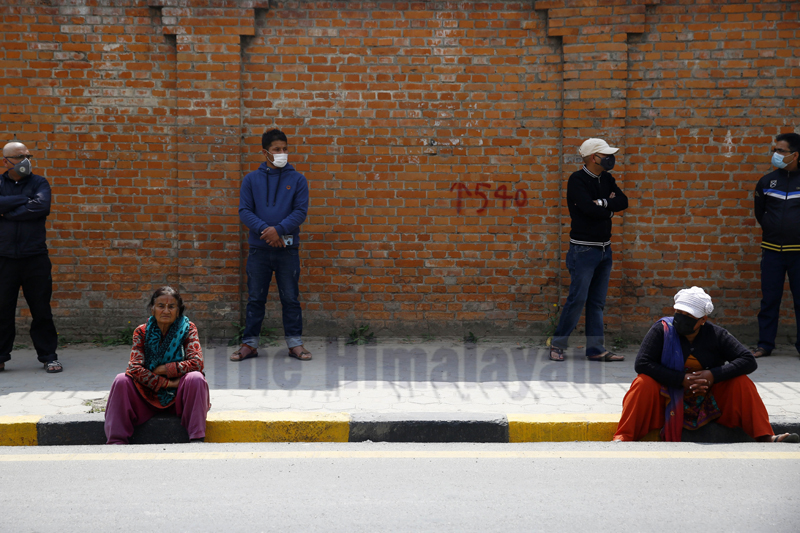 People wait along the empty streets in the hope of getting their cooking gas cylinders refilled on the second day of the week-long nationwide lockdown, in Kathmandu, on Wednesday, March 25, 2020. Photo: Skanda Gautam/THT