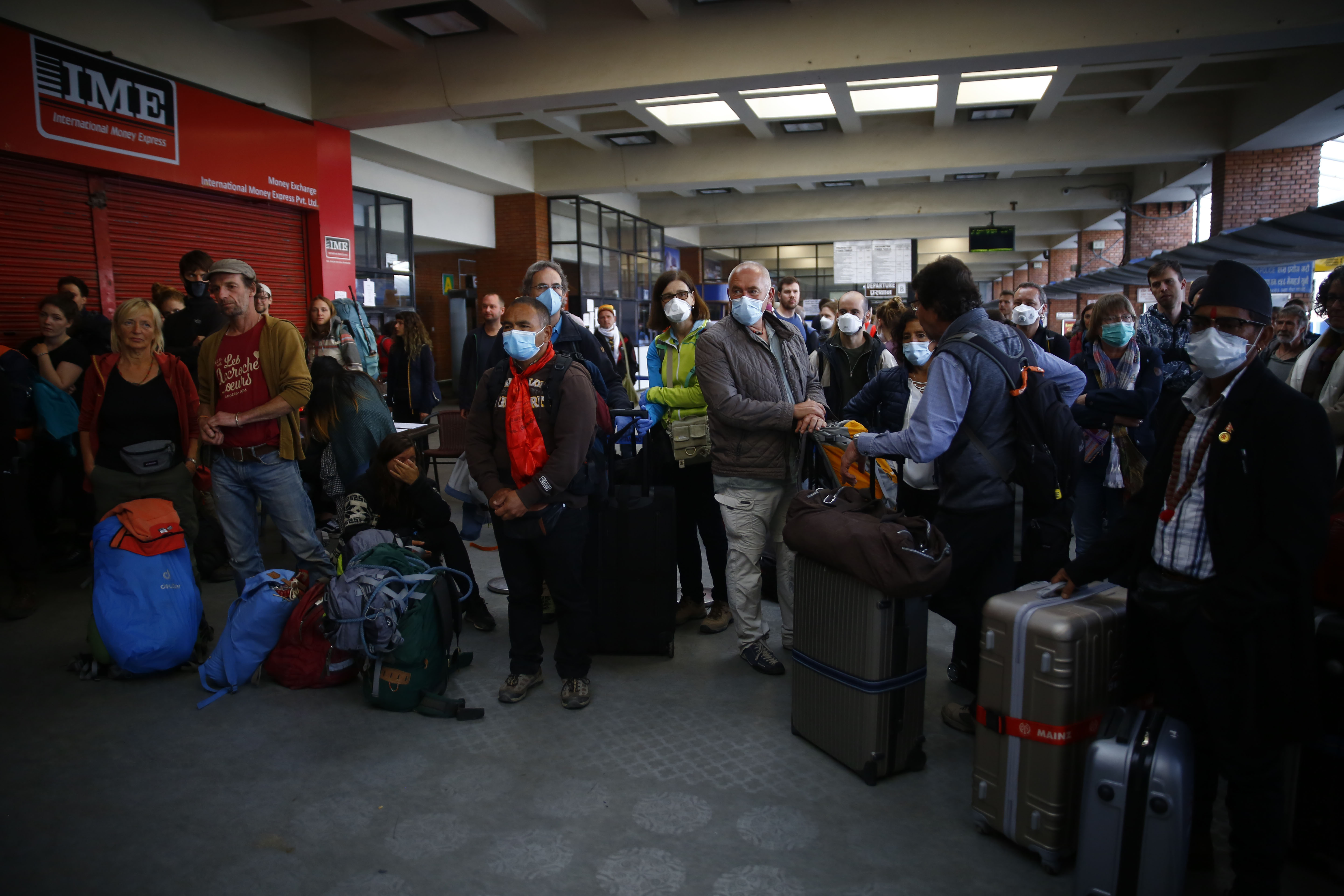 Tourists from Germany, who have been stranded in Nepal due to the government-imposed lockdown amid concerns over the spread of coronavirus infection, wait for their chartered flight back home, at Tribhuvan International Airport, in Kathmandu, on Friday, March 27, 2020. Photo: Skanda Gautam/THT