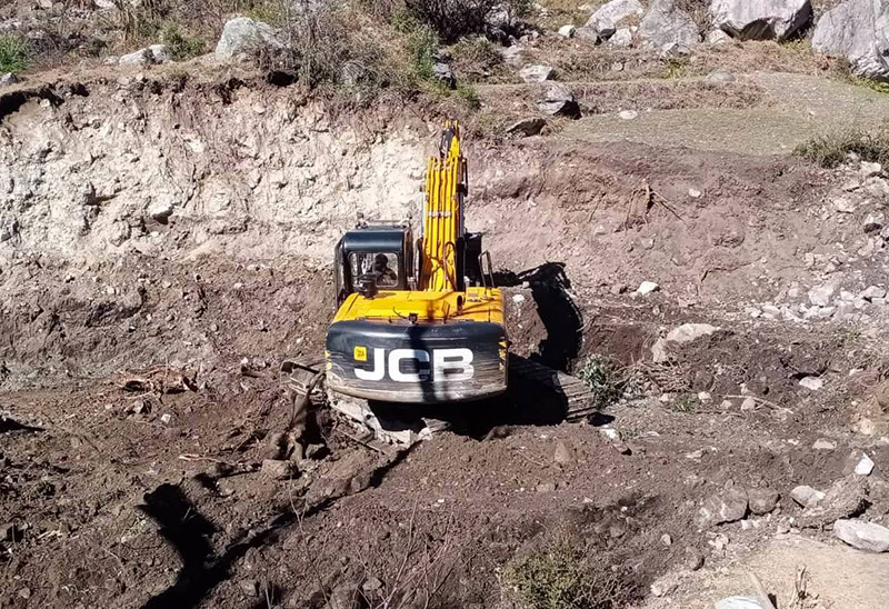 A construction vehicle being used to widen the road before blacktopping the Martadi-Kolti road section. Photo: Prakash Singh/THT