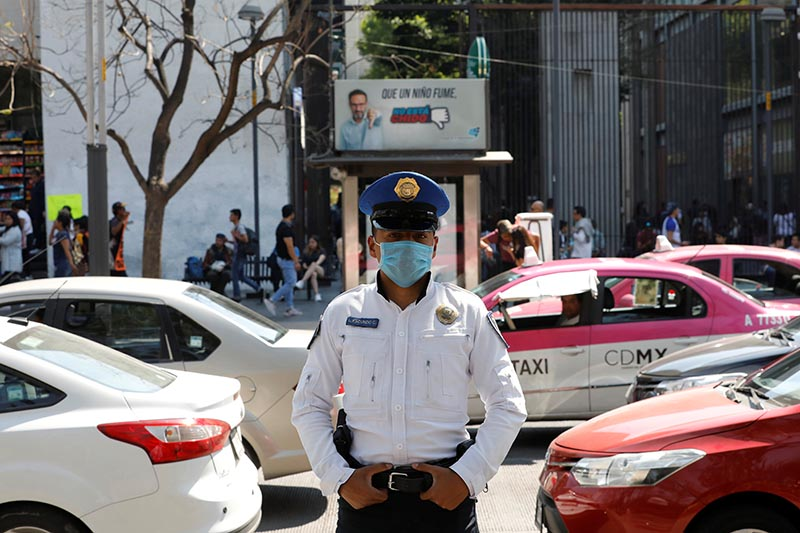 FILE - A police officer wears a protective face mask on the street after the governor of the northern Mexican state of Coahuila said on Saturday that a new case of coronavirus had been confirmed, in Mexico City, Mexico February 29, 2020. Photo: Reuters