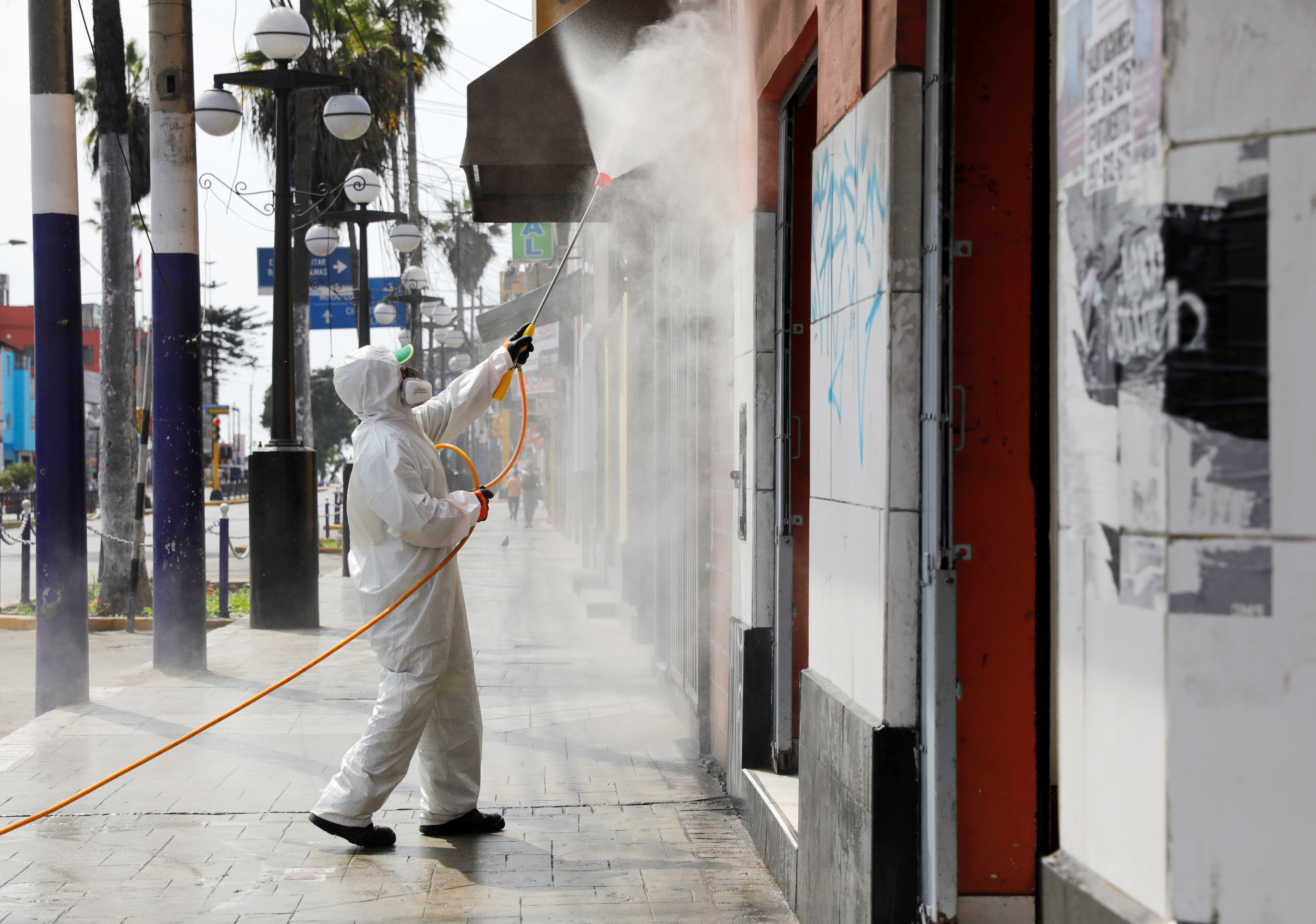 A municipal worker cleans the streets and facades in the Chorrillos neighborhood as Peru's government considers extending the days of the state of emergency and curfew to stop the spread of the coronavirus disease (COVID-19), in Lima, Peru March 21, 2020. Picture taken March 21, 2020.  Photo: Reuters