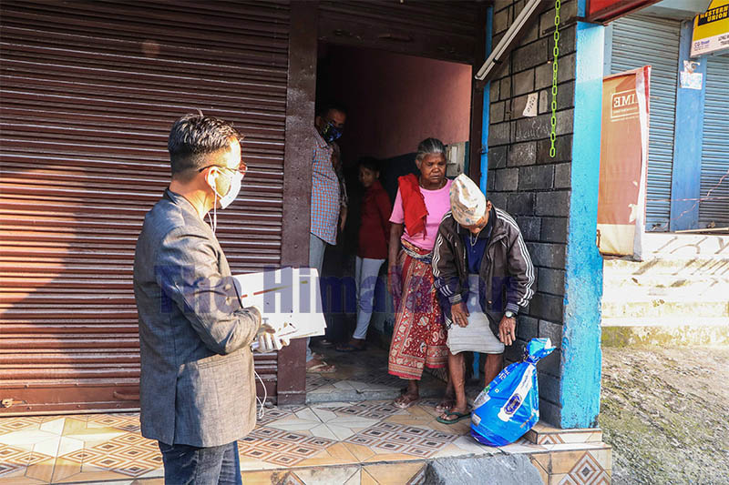 Darshan Lama (right) ward chair of Pokhara metropolis-13, donates relief package to an impoverished family, in Pokhara, on Tuesday, March 31, 2020. Photo: Rishi Ram Baral/THT