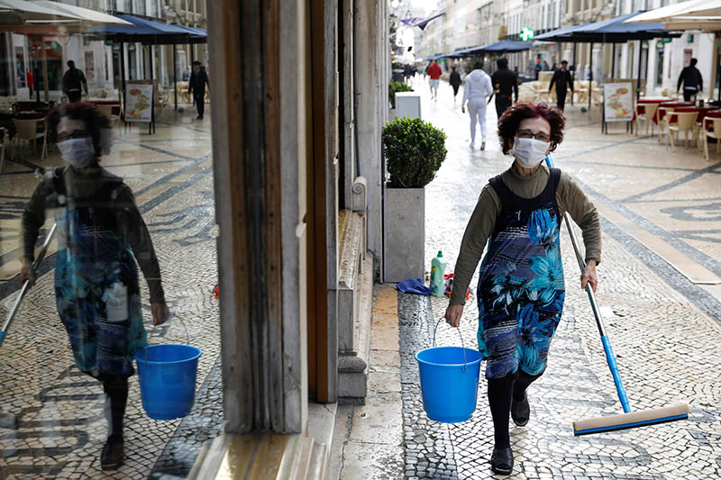 A cleaner is pictured wearing a mask, as she works at a shop in downtown Lisbon, Portugal March 16, 2020.  Photo: Reuters