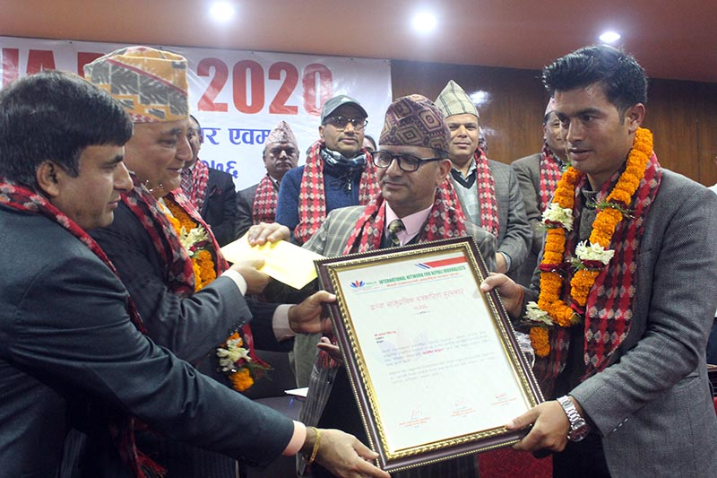 The Himalayan Times Bajura reporter Prakash Singh (right) receiving letter of appreciation from Deputy Prime Minister and Minister of Defence Ishwor Pokhrel at a programme organised in Kathmandu, on Sunday, March 1, 2020. Photo: THT