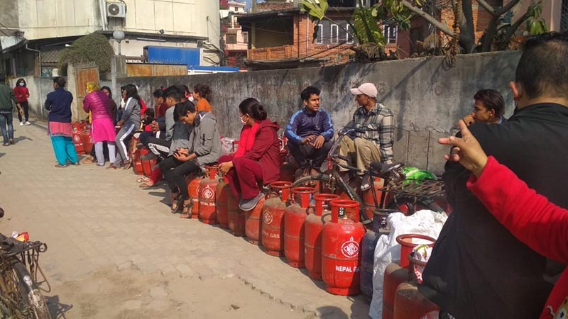 Consumers sitting on LPG cylinders and waiting for their turn in a queue to purchase the cooking gas at a retail store in Anamnagar, Kathmandu, on Friday, March 6, 2020. The assurance by traders and government officials that there is sufficient stock of essential goods has not dissuaded consumers from panic buying. Photo: Suresh Chaudhary/THT