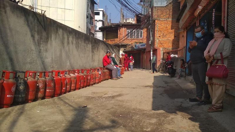 Consumers sitting on LPG cylinders and waiting for their turn in a queue to purchase the cooking gas at a retail store in Anamnagar, Kathmandu, on Friday, March 6, 2020. Photo: Suresh Chaudhary/THT