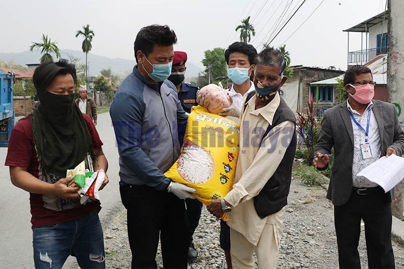 Dharan Sub-Metropolitan Ward-5 Chair Santosh Limbu (left) hand-overs relief items to economically vulnerable people hit hard by lockdown in Dharan, on Friday, March 27, 2020. Photo: Santosh Kafle/THT
