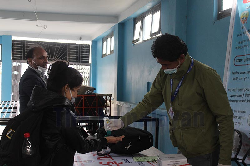 A health worker providing sanitiser to a passenger at the help desk set up at Simara Airport, in Bara, on Saturday. Photo: THT