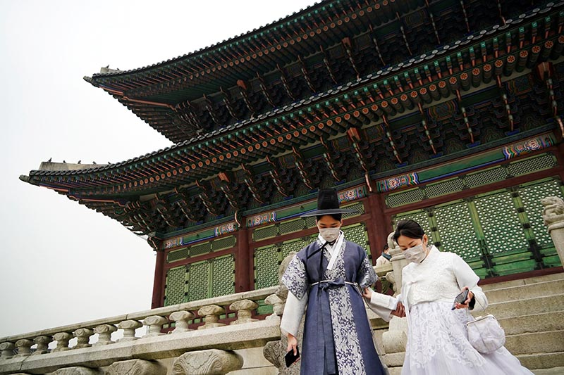 A couple in Korean traditional costumes, Hanbok, wearing masks to prevent contacting the coronavirus, walks at Gyeongbok Palace in central Seoul, South Korea, March 1, 2020. Photo: Reuters