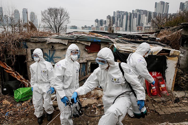 South Korean soldiers in protective gears sanitize shacks as a luxury high-rise apartment complex is seen in the background at Guryong village in Seoul, South Korea, March 3, 2020. Photo: Reuters