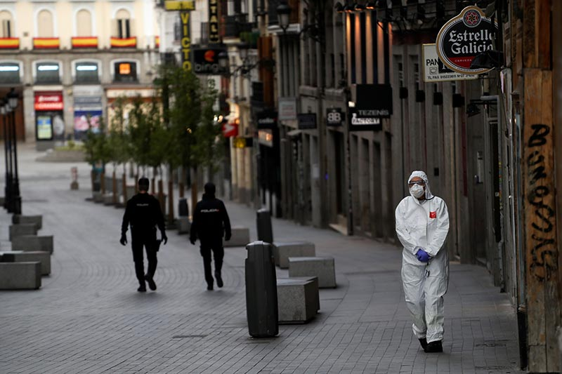 FILE - A medical worker in a protective suit walks past police officers patrolling a deserted street during the coronavirus disease (COVID-19) outbreak in Madrid, Spain March 22, 2020. Photo: Reuters