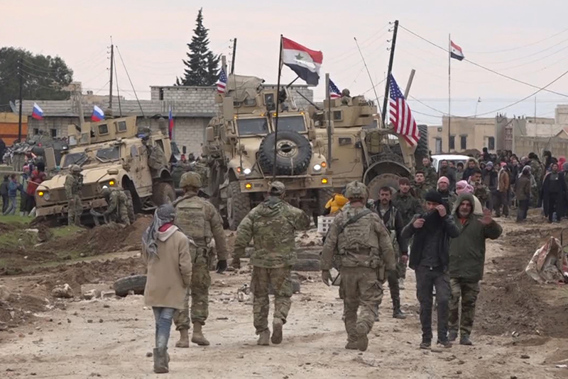 Russian, Syrian and others gather next to an American military convoy stuck in the village of Khirbet Ammu, east of Qamishli city, Syria, Feb 12, 2020. Photo: AP/File)