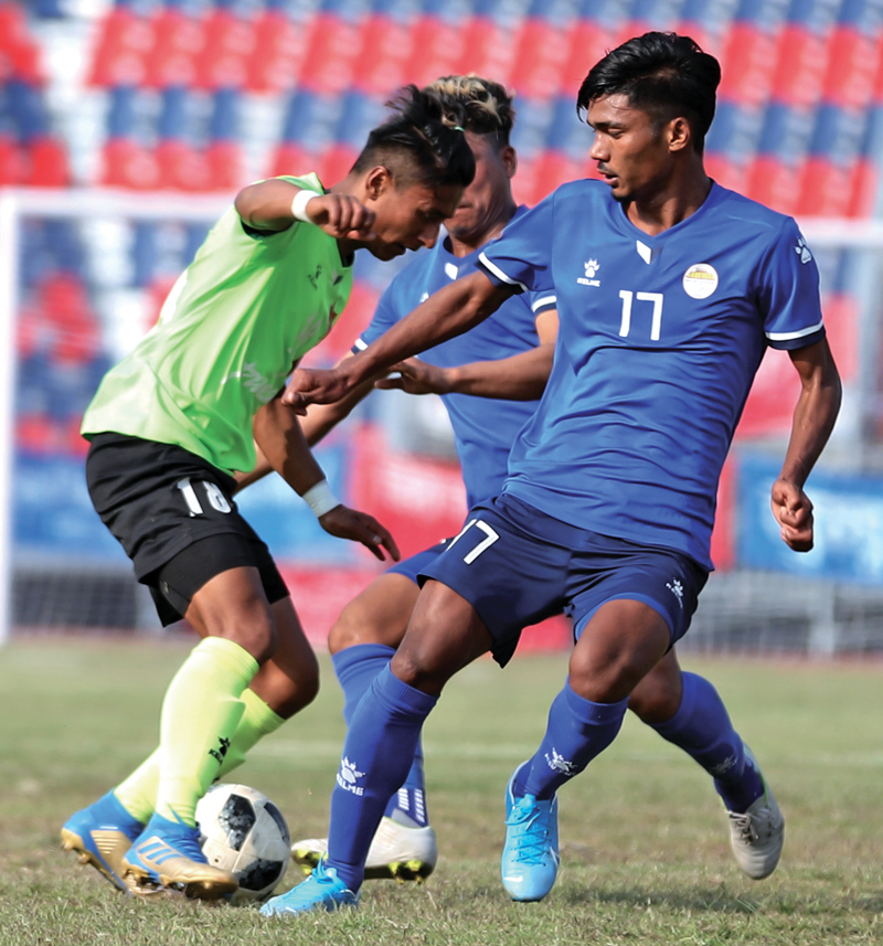 Tribhuvan Army Clubu0092s Nawayug Shrestha vies for the ball with Sankata Club players during their quarter-final match of the 18th Aaha-Rara Gold Cup Football Tournament at the Pokhara Stadium in Kaski on Tuesday. TAC won the match 3-0. Photo Courtesy: Sudarshan Ranjit