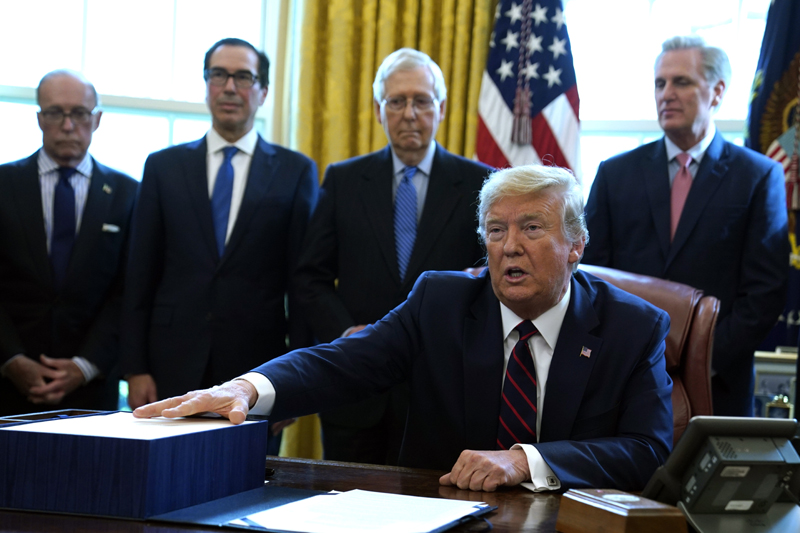 President Donald Trump speaks before he signs the coronavirus stimulus relief package in the Oval Office at the White House, Friday, March 27, 2020, in Washington. Listening are from left, Larry Kudlow, White House chief economic adviser, Treasury Secretary Steven Mnuchin, Senate Majority Leader Mitch McConnell, R-Ky., and House Minority Leader Kevin McCarty of Calif. Photo: AP