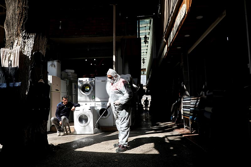 A worker in a protective suit sprays disinfectant at a market place to prevent the spread of coronavirus disease (COVID-19), in Diyarbakir, Turkey, March 23, 2020. Photo: Reuters