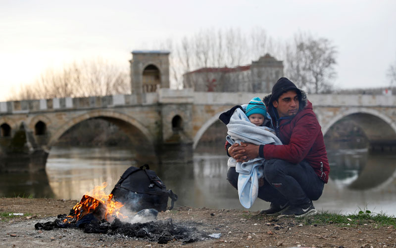 A migrant rests with a child in his arms next to the Tunca river in Edirne, Turkey, March 4, 2020. Photo: Reuters