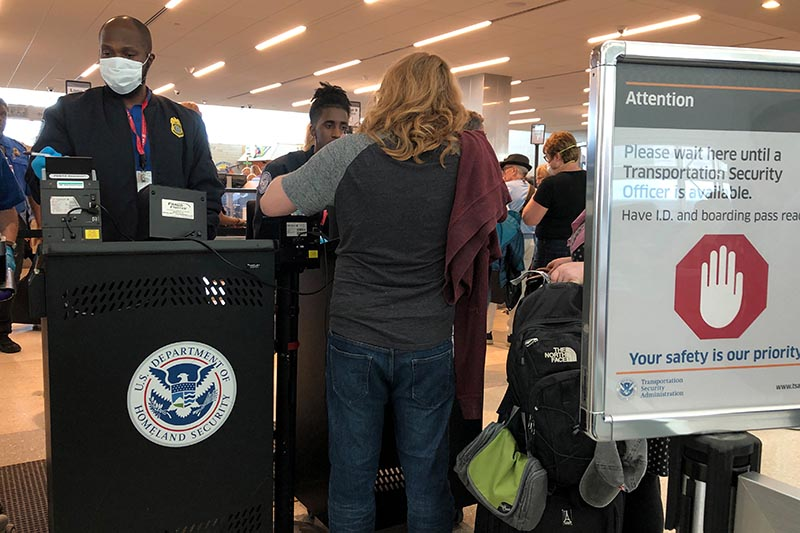 A US Department of Homeland Security officer wears a protective face mask amid coronavirus fears as he checks passports for those departing from Fort Lauderdale-Hollywood International Airport in Fort Lauderdale, Florida, US, March 15, 2020. Photo: Reuters