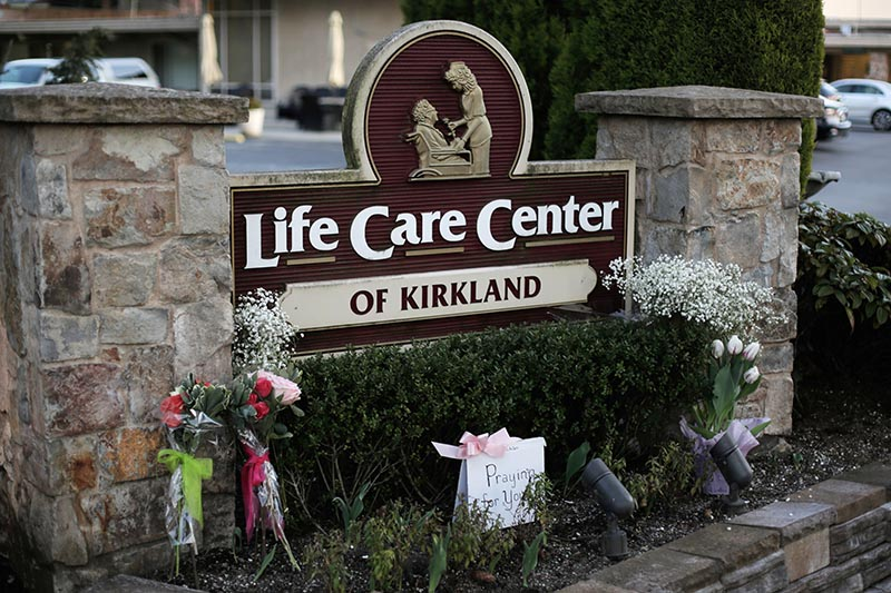 A homemade sign and flowers from community members are seen near the entrance to the Life Care Center of Kirkland, the long-term care facility linked to several confirmed coronavirus cases in the state, in Kirkland, Washington, US March 9, 2020.  Photo: Reuters