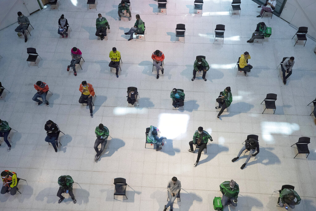 People practice social distancing as they sit on chairs spread apart in a waiting area for take-away food orders at a shopping mall in hopes of preventing the spread of the coronavirus in Bangkok, Thailand, on Tuesday, March 24, 2020. Photo: AP