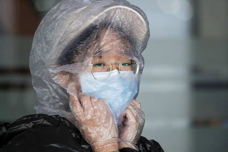 A Chinese woman uses a plastic bag to cover her head while waiting for her flight at the departure area of Manila's International Airport, Philippines, on Wednesday, March 18, 2020. The Philippine government lifted a 72-hour deadline for thousands of foreign travellers to leave the country's main northern region which has been placed under quarantine due to the growing number of coronavirus infections, officials said. Photo: AP
