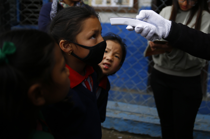 A staffer at a school checks the temperature of children as a precaution against the coronavirus outbreak, at Saipal Academy, in Sukedhara, Kathmandu, on Friday, March 6, 2020. Photo: Skanda Gautam/THT