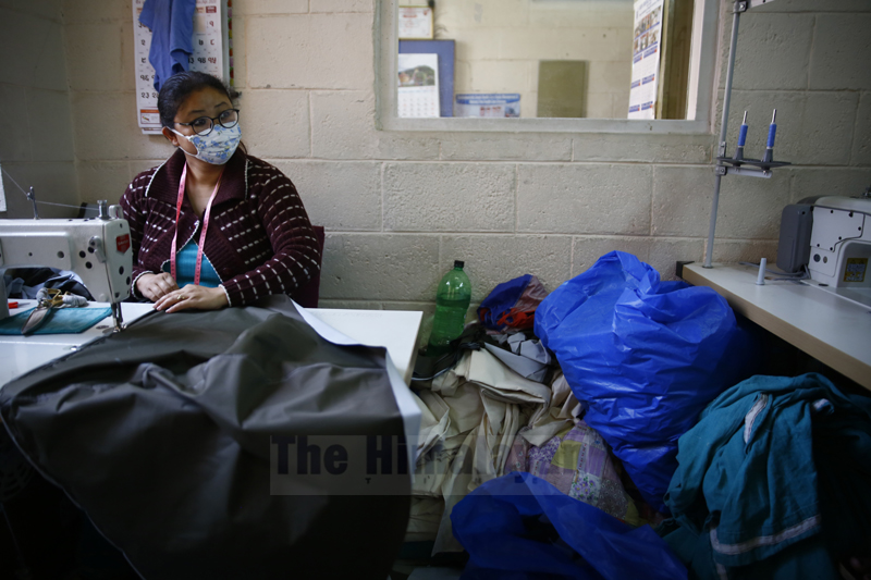A health worker makes personal protective equipment for the health workers at Patan Hospital on the third day of the nationwide lockdown amid concerns over the spread of coronavirus (COVID-19) in Lalitpur, on Thursday, March 26, 2020. Photo: Skanda Gautam/THT
