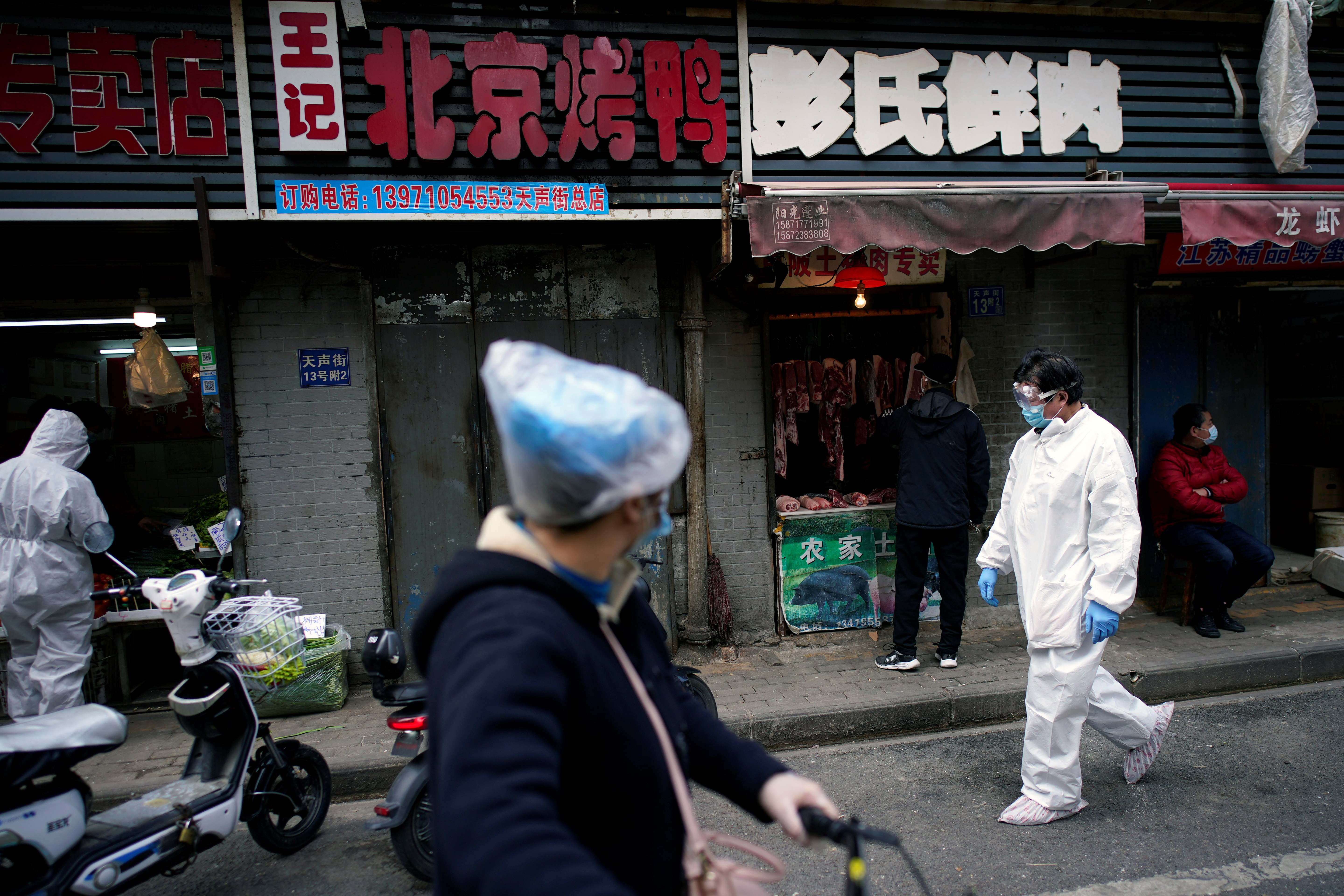 People wearing protective suits is seen at a street market in Wuhan, Hubei province, the epicentre of China's novel coronavirus disease (COVID-19) outbreak, April 6, 2020. Photo: Reuters