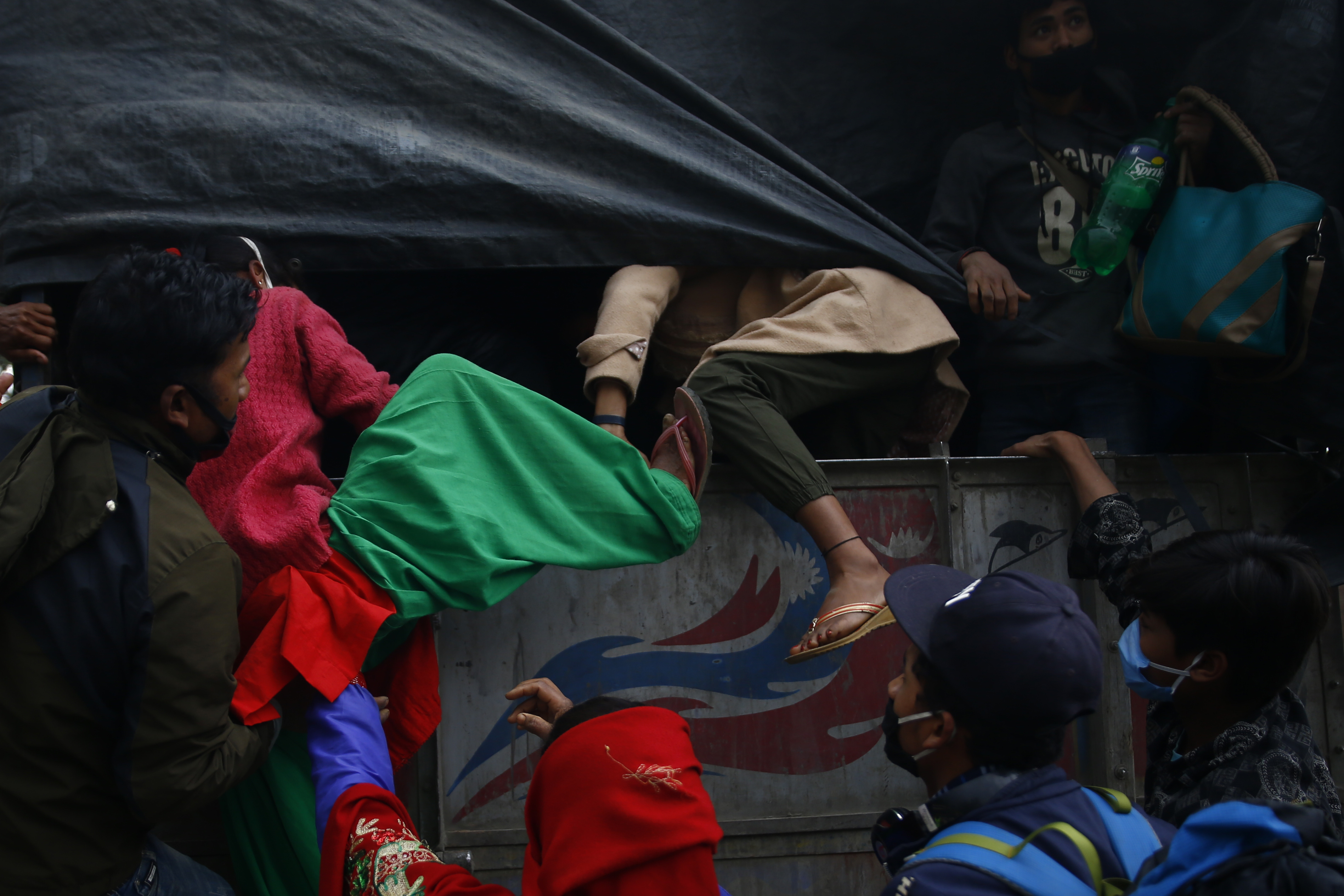 A group of stranded daily wagers get on a truck to head to their villages on the 27th day of the government imposed lockdown amid concerns over the spread of coronavirus outbreak in Bhaktapur on Sunday, April 19, 2020. Photo: Skanda Gautam/THT