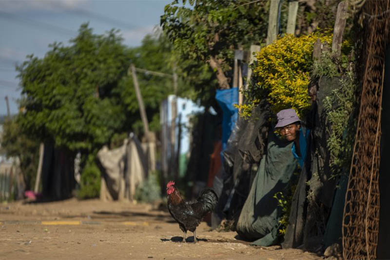 A woman watches as the South African National Defence Forces members patrol the street in Diepsloot informal settlement, north of Johannesburg, South Africa, Thursday, April 16, 2020. Photo: AP