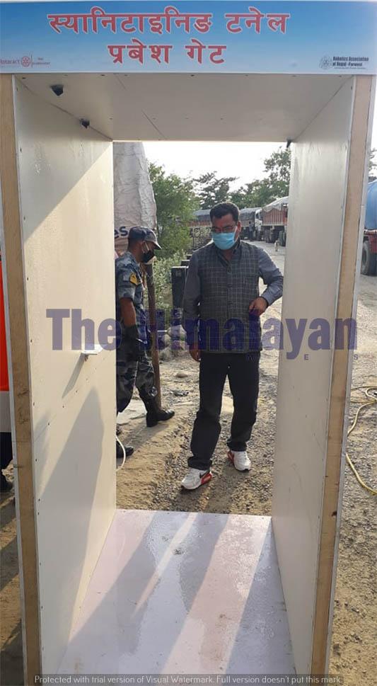 A man prepares to walk through an automatic sanitizer dispenser in Dhangadhi, along Nepal-India border point, on Tuesday, April 28, 2020. Photo: Tekendra Deuba/THT