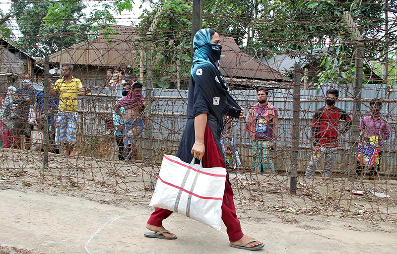 A woman, who lives near India-Bangladesh international border, carries a bag with free grocery items distributed by government officials during an extended nationwide lockdown to slow the spreading of coronavirus disease (COVID-19), at Joynagar village, on the outskirt of Agartala, India, April 17, 2020. Photo: Reuters